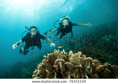 Young couple scuba dive together on a coral reef - stock photo