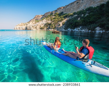 Young couple sea kayaking near the mountain coast. - stock photo