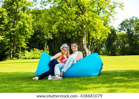 Young couple seated on a couch in a grass,bicycles in the background.Lamzac - stock photo