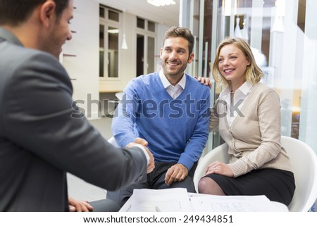 Young couple shaking hand real-estate agent in agency office - stock photo