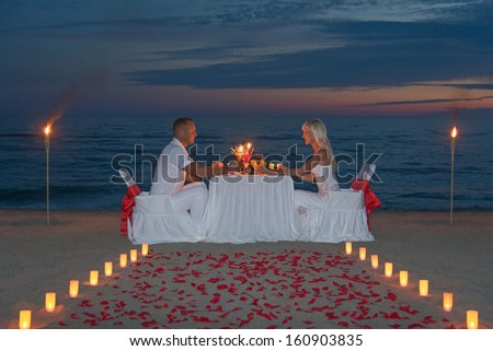 Young couple share a romantic dinner with candles, torches and way or rose petals on sea sandy beach against sunset - wedding day, proposal of marriage or honeymoon concept