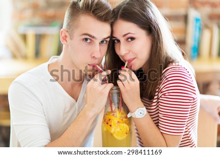 Young couple sharing a drink  - stock photo