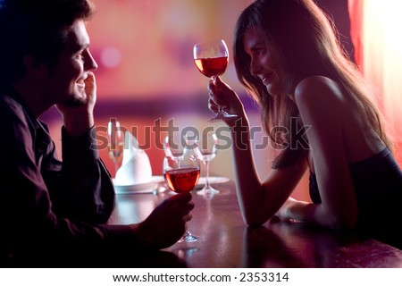 Young couple sharing a glass of red wine in restaurant, celebrating or on romantic date. Focus on woman with glass. - stock photo