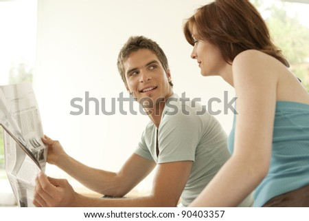 Young couple sharing a newspaper at home and talking.