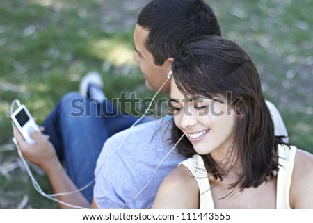 Young couple sharing and listening to music device