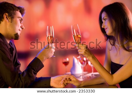 Young couple sharing champagne glasses in restaurant, celebrating or on romantic date - stock photo
