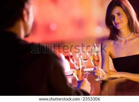 Young couple sharing champagne glasses in restaurant, celebrating or on romantic date. Focus on woman. - stock photo