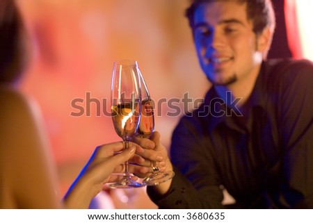 Young couple sharing champagne glasses in restaurant, celebrating or on romantic date. Focus on glasses. - stock photo