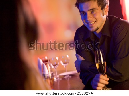 Young couple sharing champagne glasses in restaurant, celebrating or on romantic date. Focus on man.