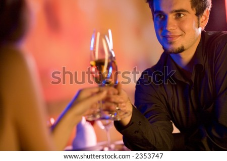 Young couple sharing champagne glasses in restaurant, celebrating or on romantic date. Focus on man. - stock photo