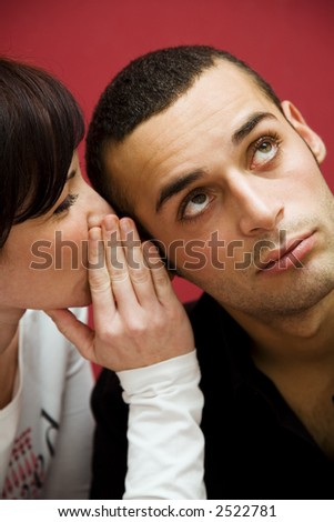 young couple: she is telling his boyfriend some cool gossip - stock photo