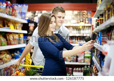 Young couple shopping at supermarket - stock photo