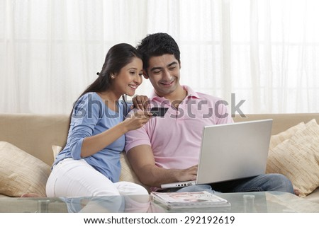 Young couple shopping online at home - stock photo