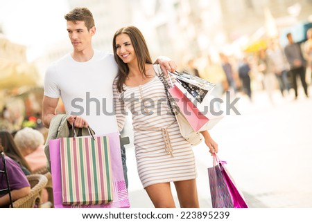 Young couple shopping walks through the city viewed the windows of boutiques, carrying shopping bags in their hands. - stock photo