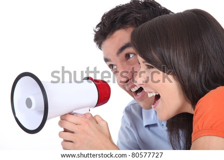 Young couple shouting into a megaphone - stock photo