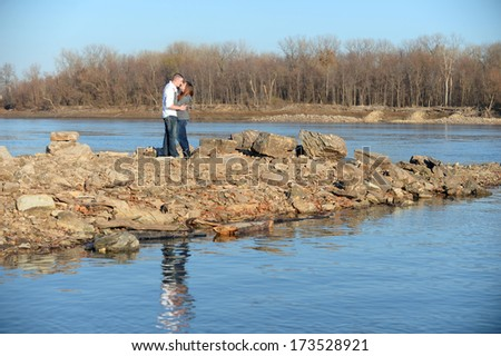 Young couple showing affection near a river
