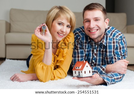 Young couple showing keys and new house miniature. - stock photo