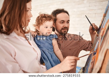 Young couple showing their little daughter how to paint - stock photo