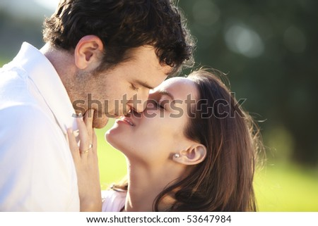 Young couple showing their love outdoors. - stock photo