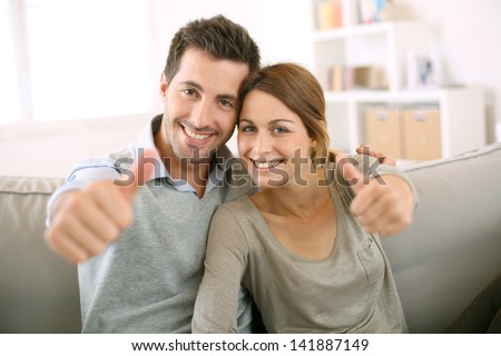 Young couple showing thumbs up - stock photo