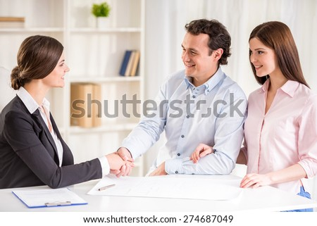 Young couple signing financial contract with female realtor. - stock photo