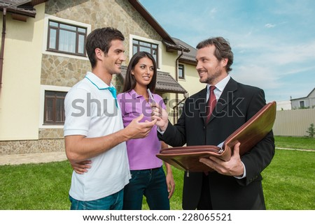 Young couple signing renting contract with real estate agent. agent giving pen to sign agreement for house sale - stock photo