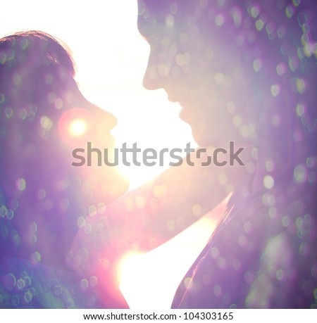 Young couple silhouette hugging and looking at each other outdoors at night neon city background - stock photo