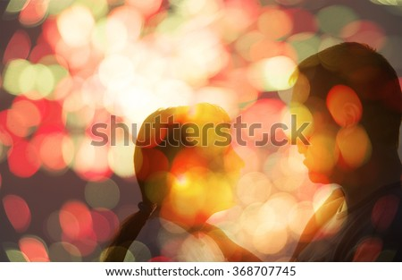 Young couple silhouette hugging and looking at each other outdoors at night neon city background. Bokeh between kissing lips.