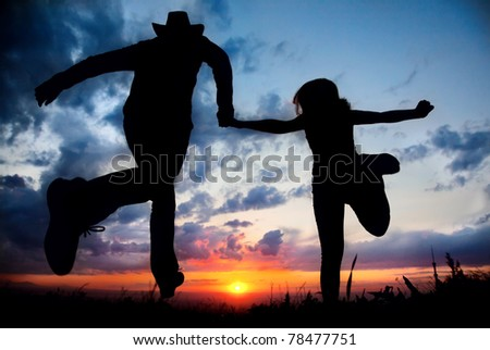 Young couple silhouette running toward the sun outdoors at sunset dramatic sky background. Man in cowboy hat holding hand of woman - stock photo