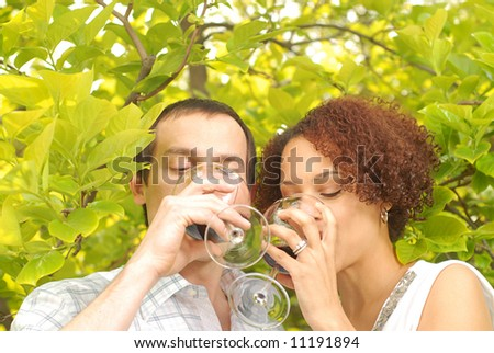 Young couple sipping wine in a garden on a summer picnic