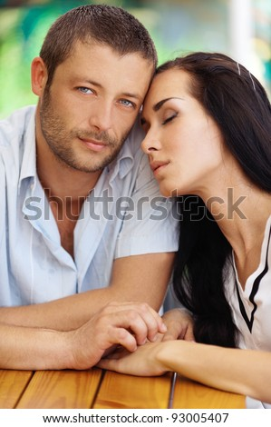 Young couple sit at little table in summer cafe. - stock photo