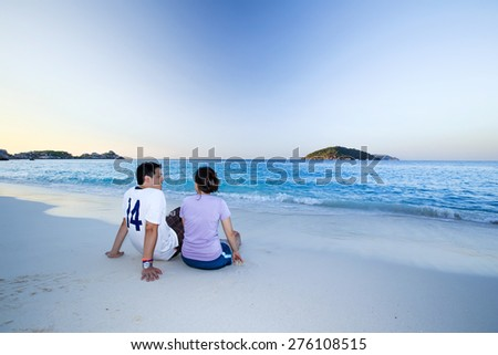 young couple sit on the beach look at the beautiful sunset - stock photo