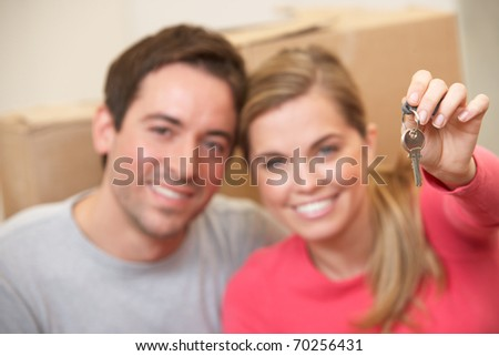 Young couple sit on the floor around boxes holding key in hand - stock photo