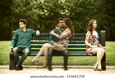 Young couple sits apart on the bench in the park and remembers their love story - stock photo