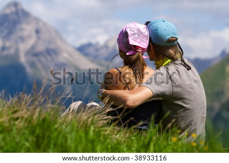 Young couple sitting and enjoying a mountains view - stock photo