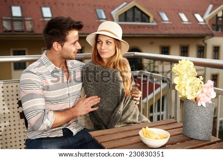 Young couple sitting and hugging on terrace, smiling. - stock photo