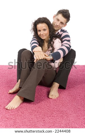 young couple sitting and snuggling on the pink carpet - stock photo
