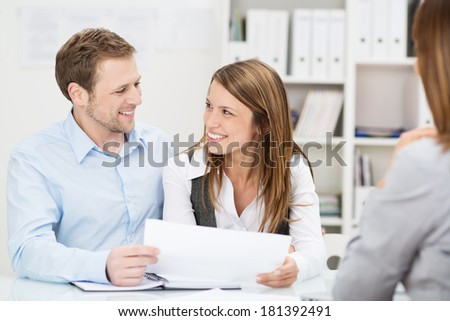 Young couple sitting at a desk in the office of their agent or adviser discussing an investment presentation on a document they are holding - stock photo