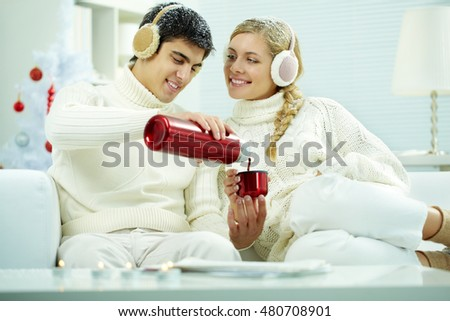 Young couple sitting at home in snow and drinking tea