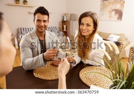 Young couple sitting at table, clinking glasses with a friend. - stock photo