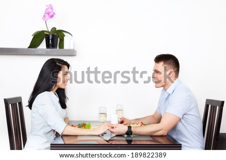 Young couple sitting at table holding hands, romantic dinner date - stock photo