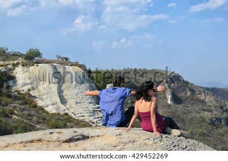 Young couple sitting at the edge of the cliff catching wind