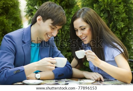 Young couple sitting at the table and drink coffee - stock photo