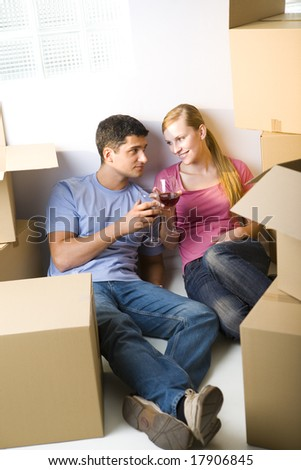 Young couple sitting between cardboard boxes and drinking wine. They're looking at each other's. Front view. - stock photo