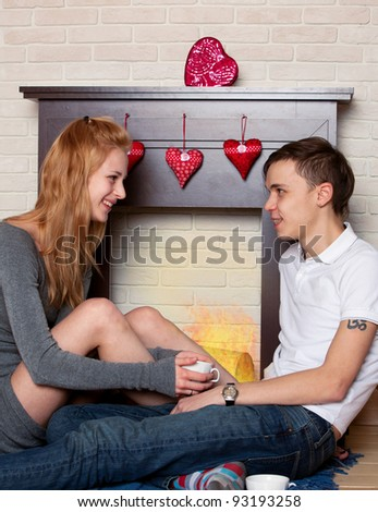 Young couple sitting by the fireplace in the st. Valentine's day