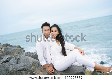 Young couple sitting by the sea and looking at camera