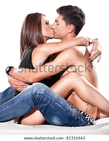 Young couple sitting close to each other,hugging and passionately kissing - stock photo