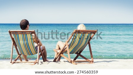 Young couple sitting in a beach chairs and looking at the sea - stock photo