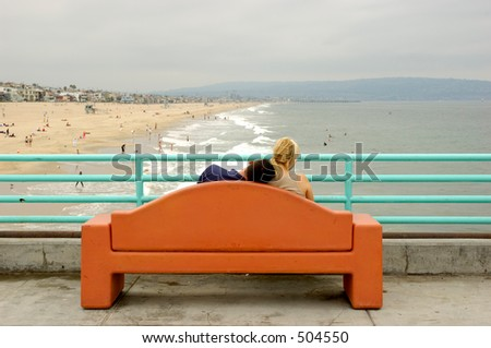 Young couple sitting in a bench over the pier. The boyfriend has his head on his girlfriend's shoulder and she is looking away to the right. - stock photo