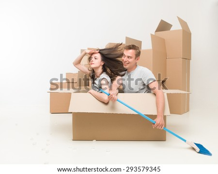young couple sitting in a box pretending they are in a boat, paddeling with a broom - stock photo